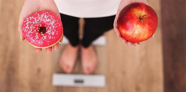 Person auf der Waage - Donut oder Apfel?