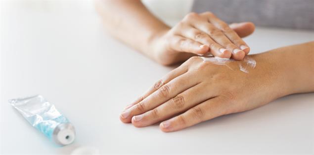Hand mit Schuppenflechte wird eingecremt