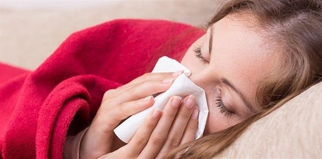 junges Mädchen mit Grippe/Erkältung putzt sich die Nase