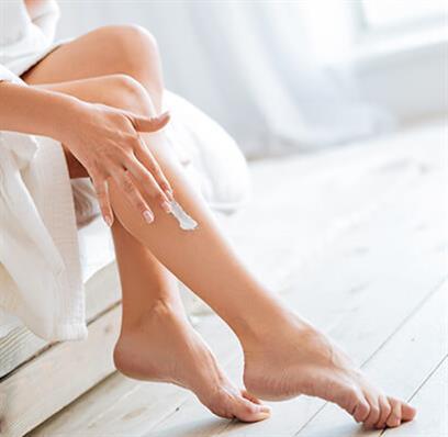 Eine Frau cremt sich die Beine mit Dermoprodukten ein