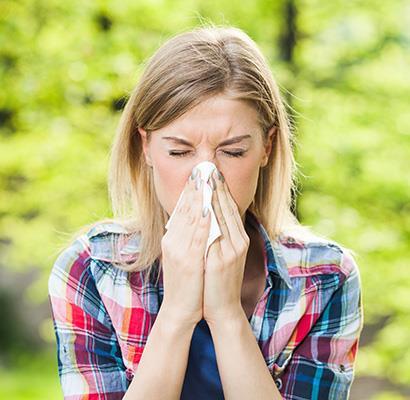 junge Frau putzt sich Nase und hat Heuschnupfen