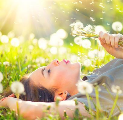 Frau liegt glücklich auf einer Blumenwiese